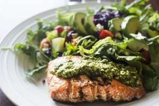 Close up of a healthy home-cooked meal on a plate which includes a grilled salmon fillet topped with arugula pesto accompanied by a green salad with avocado, romaine lettuce, cucumber, tomatoes, carrots and red cabbage.